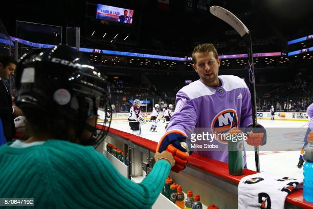 Josh Bailey of the New York Islanders fist bumps a fan while wearing a special jersey in support of Hockey Fights Cancer before a game against the...