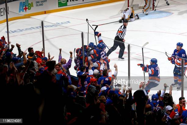 Josh Bailey of the New York Islanders is congratulated by his teammates after scoring the game winning goal in the first overtime period against the...