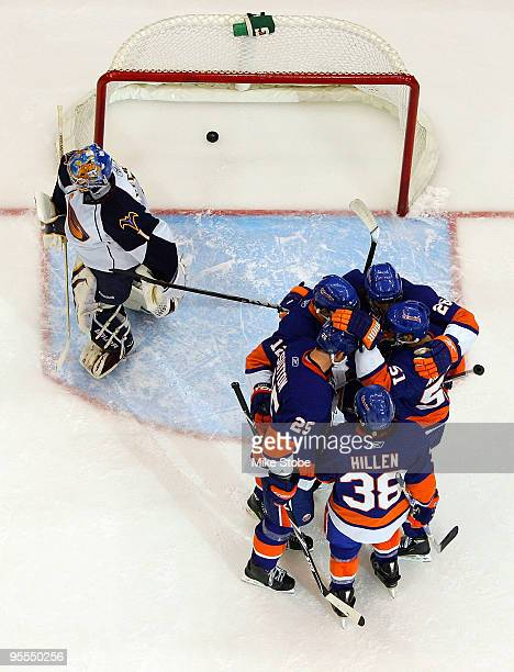 Josh Bailey of the New York Islanders is mobbed by his teammates after scoring a second period goal as Johan Hedberg of the Atlanta Thrashers skates...