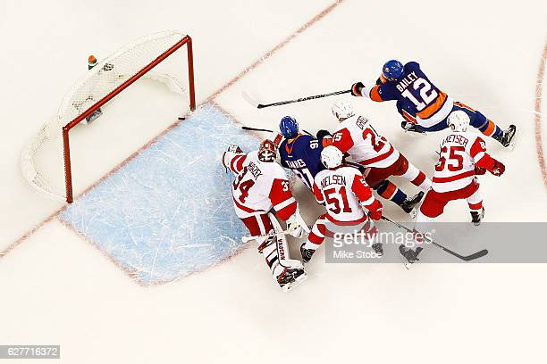 Josh Bailey of the New York Islanders score a third period goal past Petr Mrazek of the Detroit Red Wings as John Tavares looks on at the Barclays...