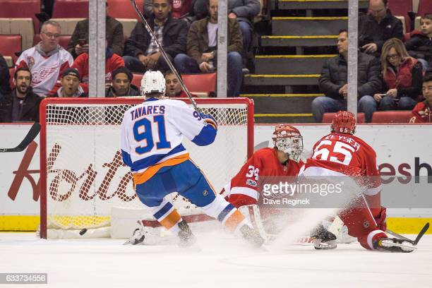Josh Bailey of the New York Islanders scores a first period goal on goaltender Petr Mrazek of the Detroit Red Wings as John Tavares of the Islanders...