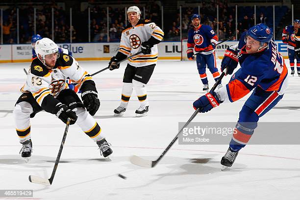 Josh Bailey of the New York Islanders takes a shot as Matt Bartkowski of the Boston Bruins defends him at Nassau Veterans Memorial Coliseum on...