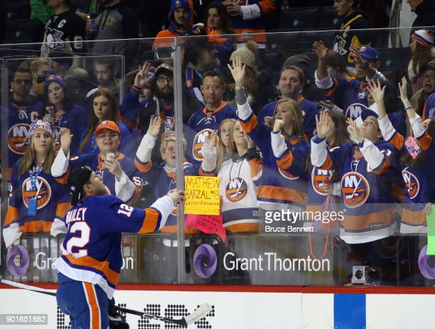 Josh Bailey of the New York Islanders tosses a puck to fans during warmups prior to the game against the Pittsburgh Penguins at the Barclays Center...