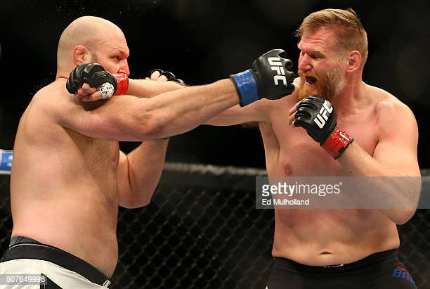 Josh Barnett exchanges punches with Ben Rothwell in their heavyweight bout during the UFC Fight Night event at the Prudential Center on January 30...