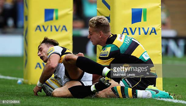Josh Bassett of Wasps beats Harry Mallinder of Northampton Saints to score a try during the Aviva Premiership match between Northampton Saints and...