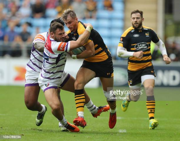 Josh Bassett of Wasps is held by Adam Thompstone and Manu Tuilagi during the Gallagher Premiership Rugby match between Wasps and Leicester Tigers at...