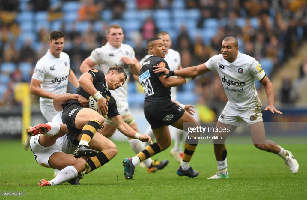 Josh Bassett of Wasps is tackled by Ben Tapuai of Bath during the Aviva Premiership match between Wasps and Bath Rugby at The Ricoh Arena on October 1, 2017 in Coventry, England.