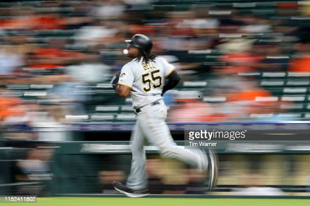 Josh Bell of the Pittsburgh Pirates blows a bubble while running to first after hitting a fly ball out in the eighth inning against the Houston...