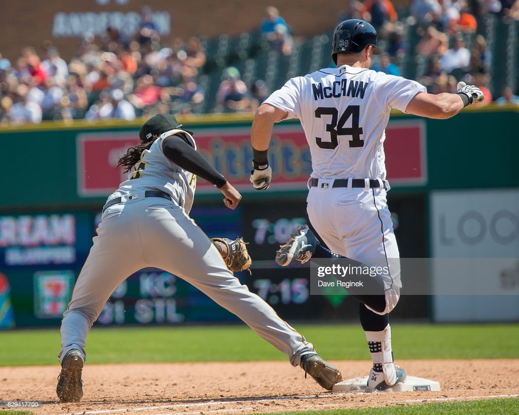 Josh Bell #55 of the Pittsburgh Pirates hangs on to the ball and gets James McCann #34 of the Detroit Tigers out at first base in the seventh inning during a MLB game at Comerica Park on August 10, 2017 in Detroit, Michigan. The Pirates defeated the Tigers 7-5.