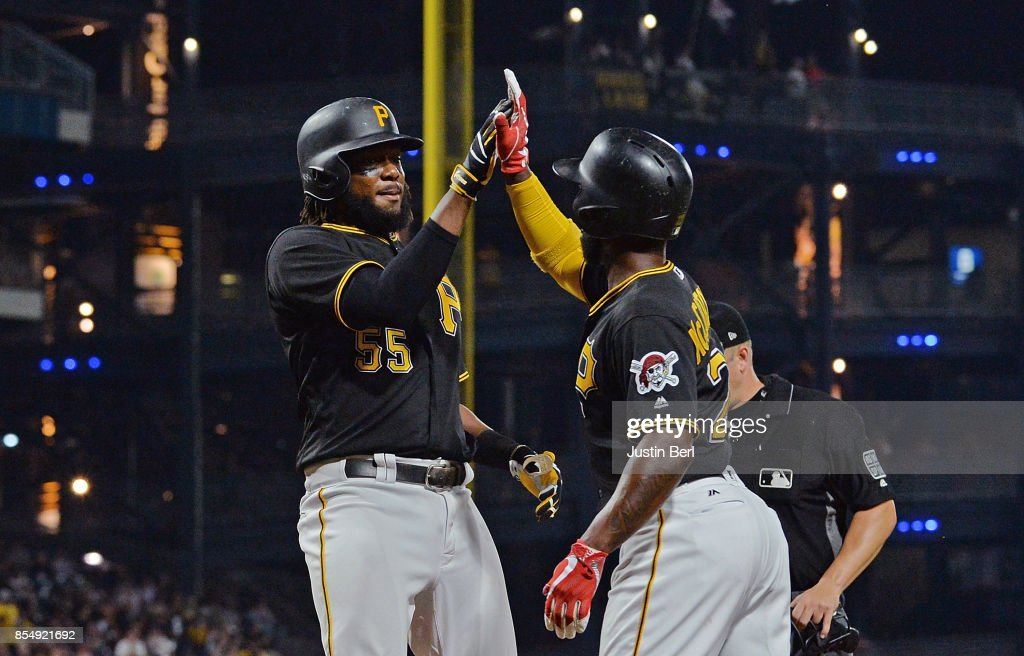 Josh Bell #55 of the Pittsburgh Pirates high fives with Andrew McCutchen #22 after hitting a two run home run in the third inning during the game against the Baltimore Orioles at PNC Park on September 27, 2017 in Pittsburgh, Pennsylvania.