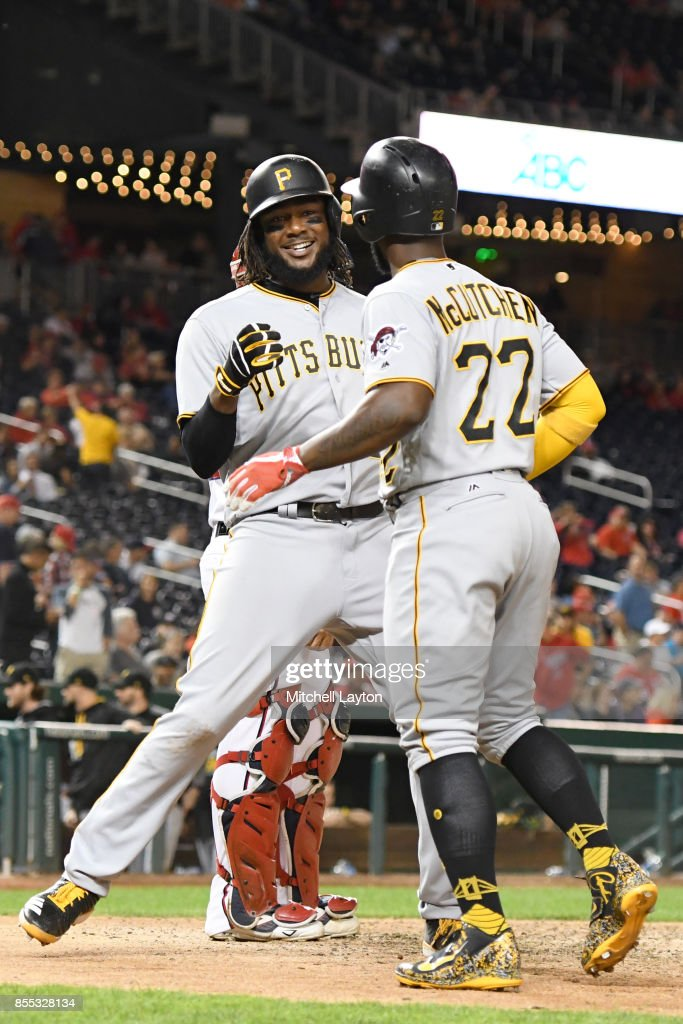 Josh Bell #55 of the Pittsburgh Pirates hits a two-run home run to tie the game in the ninth inning and celebrates with Andrew McCutchen #22 during a baseball game against the Washington Nationals at Nationals Park on September 28, 2017 in Washington, DC.