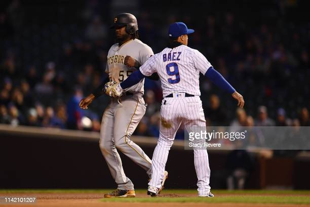 Josh Bell of the Pittsburgh Pirates is tagged out by Javier Baez of the Chicago Cubs during the fourth inning at Wrigley Field on April 11 2019 in...