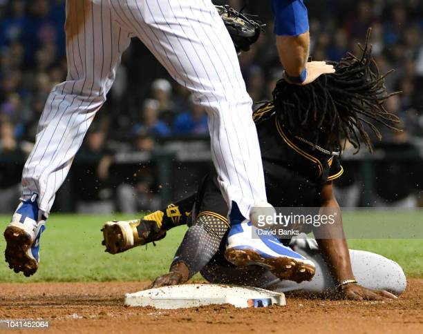 Josh Bell of the Pittsburgh Pirates slides safely into third base as David Bote of the Chicago Cubs can't handle the throw during the eighth inning...
