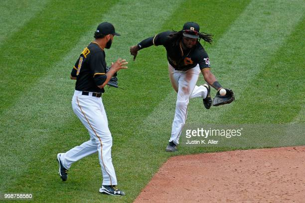 Josh Bell of the Pittsburgh Pirates tosses the ball to Richard Rodriguez to record the out in the sixth inning during game one of a doubleheader...