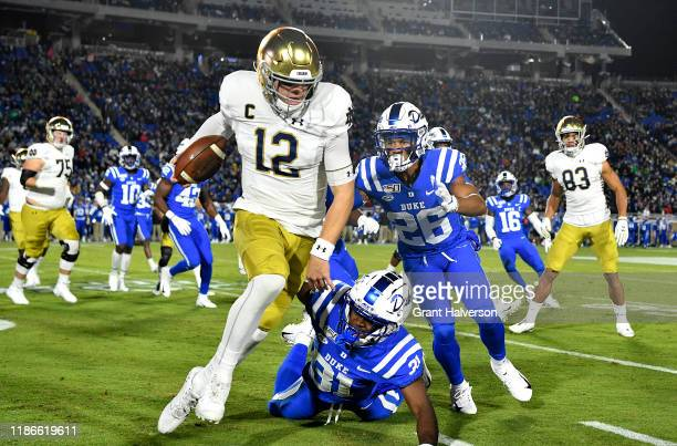 Josh Blackwell and Michael Carter II of the Duke Blue Devils chase Ian Book of the Notre Dame Fighting Irish out of bounds during the first quarter...