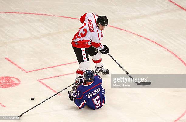 Josh Brittain of Canada and Matt Williams of the USA contest possession during the International Ice Hockey Series between the United States and...
