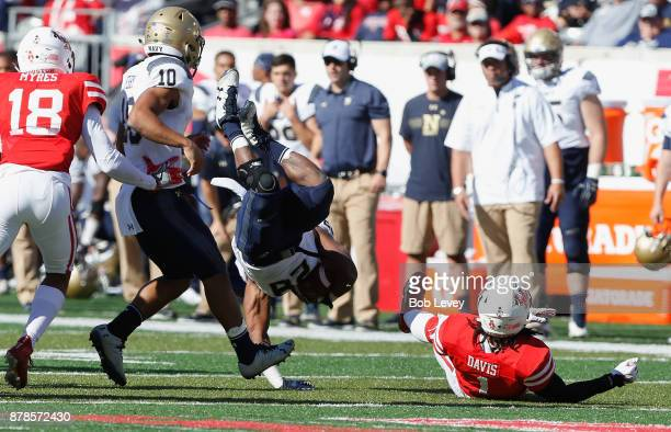 Josh Brown of the Navy Midshipmen is updended by Garrett Davis of the Houston Cougars on November 24 2017 in Houston Texas