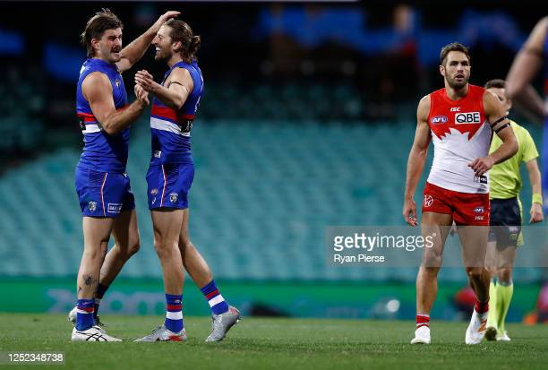 Josh Bruce of the Bulldogs celebrates a goal with Marcus Bontempelli of the Bulldogs as Josh Kennedy of the Swans looks on during the round 4 AFL...