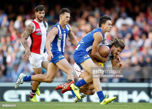 Josh Bruce of the Saints is tackled by Luke DaviesUniacke of the Kangaroos during the 2018 AFL round 02 Good Friday Kick for the Kids match between...