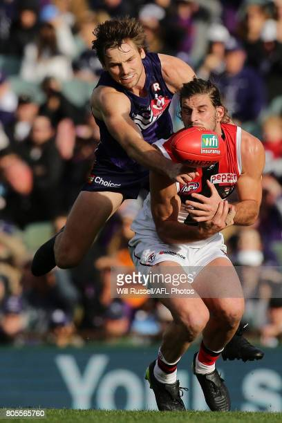 Josh Bruce of the Saints marks the ball under pressure from Joel Hamling of the Dockers during the round 15 AFL match between the Fremantle Dockers...