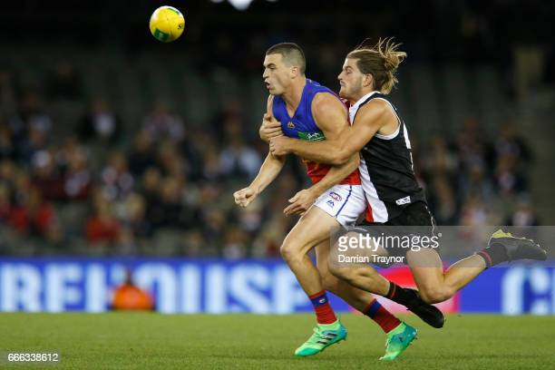 Josh Bruce of the Saints tackles Tom Rockliff of the Lions during the round three AFL match between the St Kilda Saints and the Brisbane Lions at...