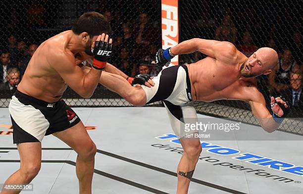 Josh Burkman of the United States kicks Patrick Cote in their welterweight bout during the UFC event at the SaskTel Centre on August 23 2015 in...