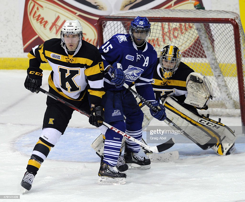 Josh Burnside #15 of the Mississauga Steelheads battles with Mikko Valnonen #5 the Kingston Frontenacs in front of Fronenacs goalie Lucas Peressini #40 during game action on March 16, 2014 at the Hershey Centre in Mississauga, Ontario, Canada.