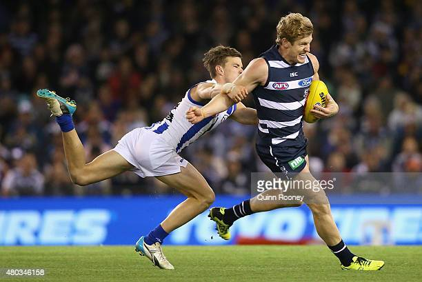 Josh Caddy of the Cats is tackled by Kayne Turner of the Kangaroos during the round 15 AFL match between the North Melbourne Kangaroos and the...