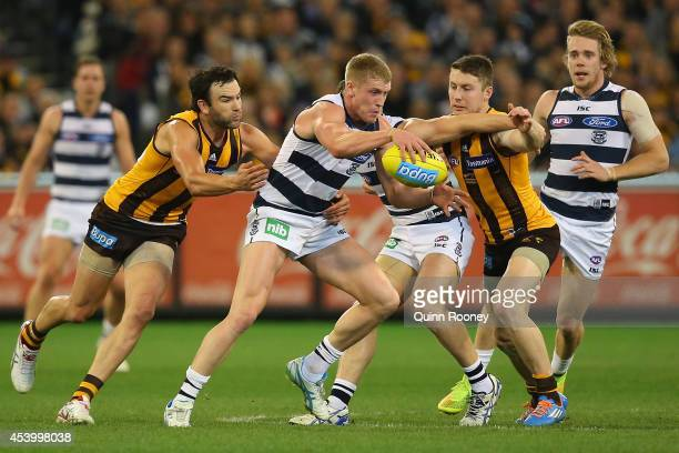 Josh Caddy of the Cats kicks whilst being tackled by Jordan Lewis and Liam Shiels of the Hawks during the round 22 AFL match between the Hawthorn...