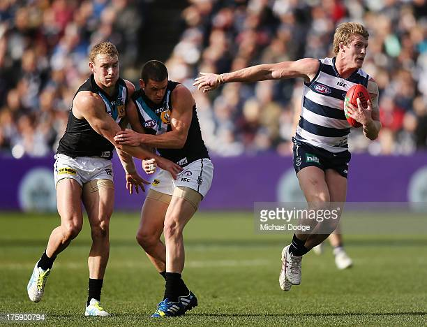 Josh Caddy of the Cats runs with the ball away from Andrew Moore and Travis Boak of Port Adelaide during the round 20 AFL match between the Geelong...