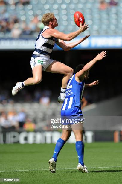 Josh Caddy of the Cats takes a high mark over Scott McMahon of the Kangaroos during the round two AFL match between the Geelong Cats and the North...
