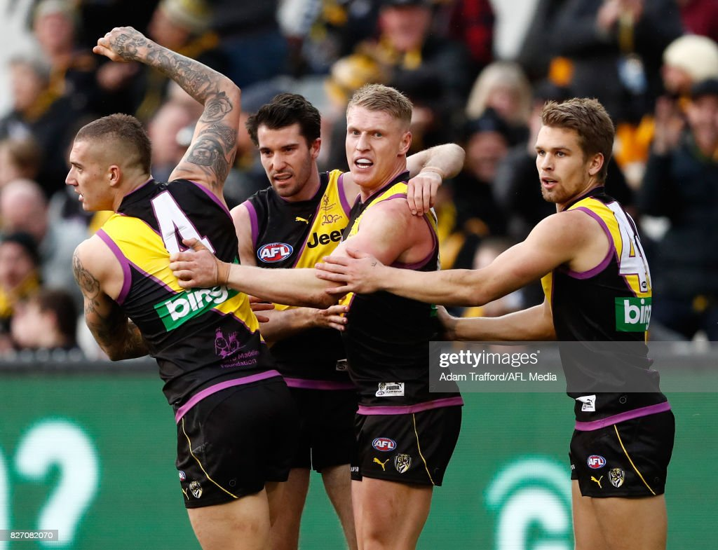 Josh Caddy of the Tigers (second from right) celebrates a goal with Dustin Martin, Corey Ellis and Dan Butler of the Tigers during the 2017 AFL round 20 match between the Richmond Tigers and the Hawthorn Hawks at the Melbourne Cricket Ground on August 06, 2017 in Melbourne, Australia.
