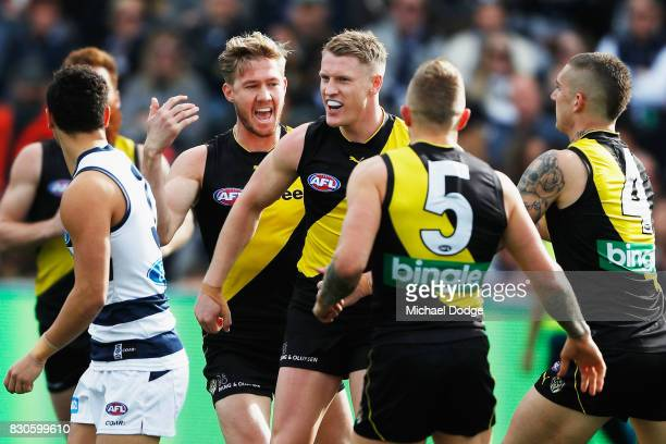 Josh Caddy of the Tigers celebrates a goal with teammmates as he reacts to Brandon Parfitt of the Cats during the round 21 AFL match between the...