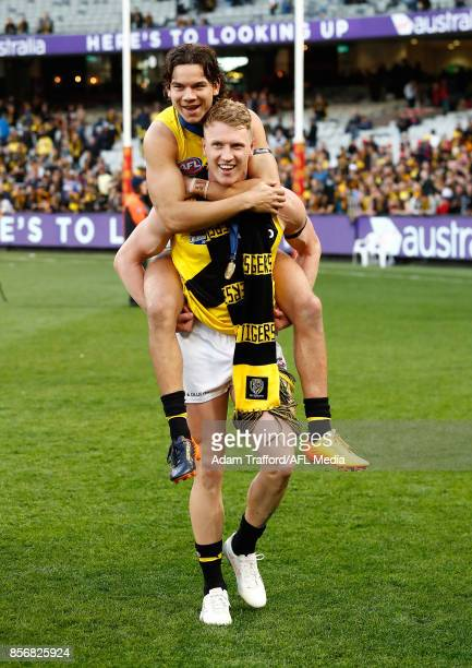Josh Caddy of the Tigers gives a piggy back to the injured Daniel Rioli of the Tigers during the 2017 Toyota AFL Grand Final match between the...