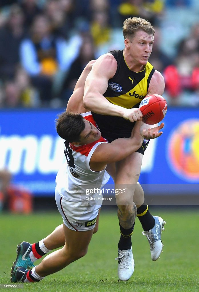 Josh Caddy of the Tigers handballs whilst being tackled by Jack Steele of the Saints during the round 10 AFL match between the Richmond Tigers and the St Kilda Saints at Melbourne Cricket Ground on May 26, 2018 in Melbourne, Australia.