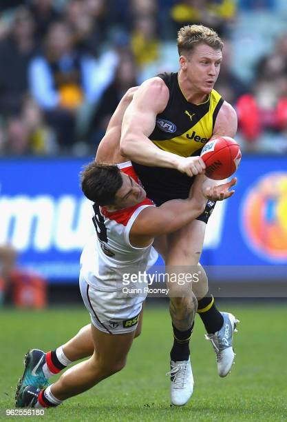 Josh Caddy of the Tigers handballs whilst being tackled by Jack Steele of the Saints during the round 10 AFL match between the Richmond Tigers and...