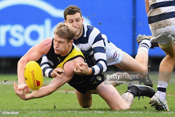 Josh Caddy of the Tigers handballs whilst being tackled by Sam Menegola of the Cats during the round 13 AFL match between the Geelong Cats and the...