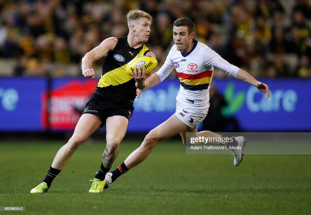 Josh Caddy of the Tigers handpasses the ball ahead of Paul Seedsman of the Crows during the 2018 AFL round 16 match between the Richmond Tigers and the Adelaide Crows at the Melbourne Cricket Ground on July 06, 2018 in Melbourne, Australia.
