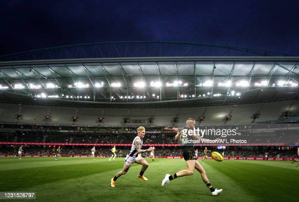 Josh Caddy of the Tigers is chased by John Noble of the Magpies during the 2021 AAMI Community Series match between the Collingwood Magpies and the...