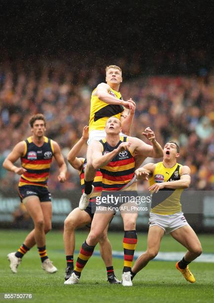 Josh Caddy of the Tigers jumps over Sam Jacobs of the Crows during the 2017 AFL Grand Final match between the Adelaide Crows and the Richmond Tigers...