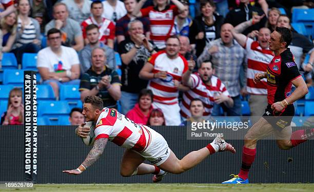 Josh Charnley of Wigan dives into score a try past Kevin Sinfield of Leeds during the Super League Magic Weekend match between Leeds Rhinos and Wigan...