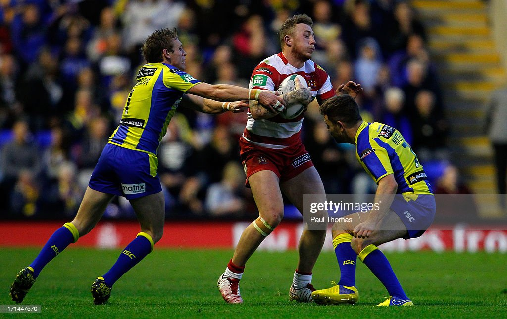 Josh Charnley of Wigan (C) is challenged by Brett Hodgson and Richie Myler (R) of Warrington during the Super League match between Warrington Wolves and Wigan Warriors at the Halliwell Jones Stadium on June 24, 2013 in Warrington, England.