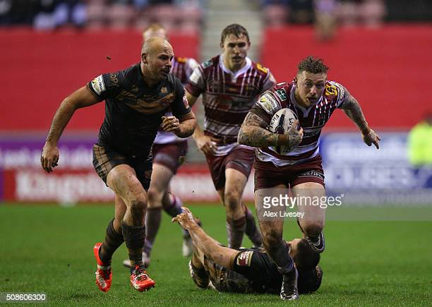 Josh Charnley of Wigan Warriors beats Julian Busquet and Glenn Stewart of Catalans Dragons during the First Utility Super League match between Wigan...