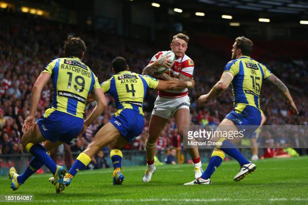 Josh Charnley of Wigan Warriors is surrounded by Stefan Ratchford Ryan Atkins and Simon Grix of Warrington Wolves during the Super League Grand Final...