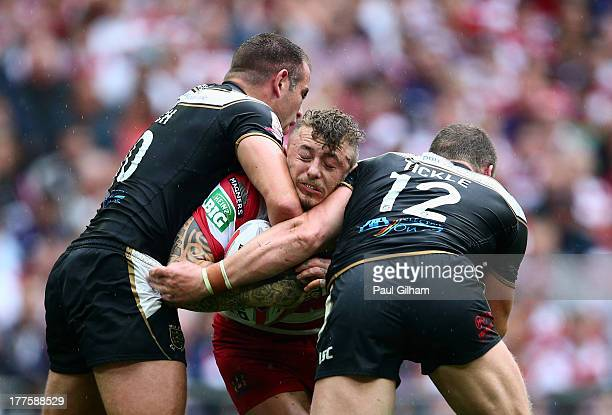 Josh Charnley of Wigan Warriors is tackled by Andy Lynch and Danny Tickle of Hull FC during the Tetley's Challenge Cup Final between Wigan Warriors...