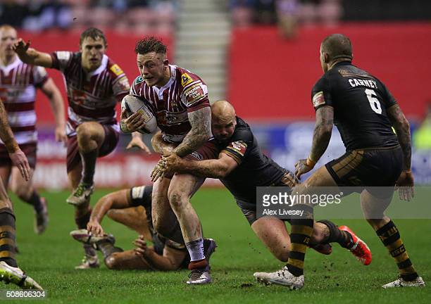 Josh Charnley of Wigan Warriors is tackled by Glenn Stewart of Catalans Dragons during the First Utility Super League match between Wigan Warriors...
