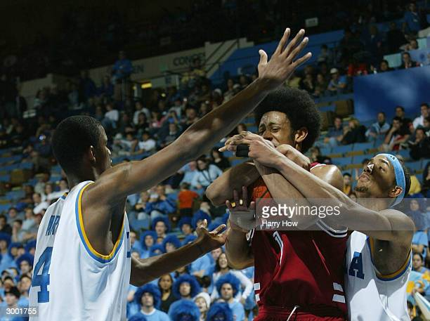 Josh Childress of Stanford is surrounded with the ball by Dijon Thompson and Trevor Ariza of UCLA in the second half during the game at Pauley...
