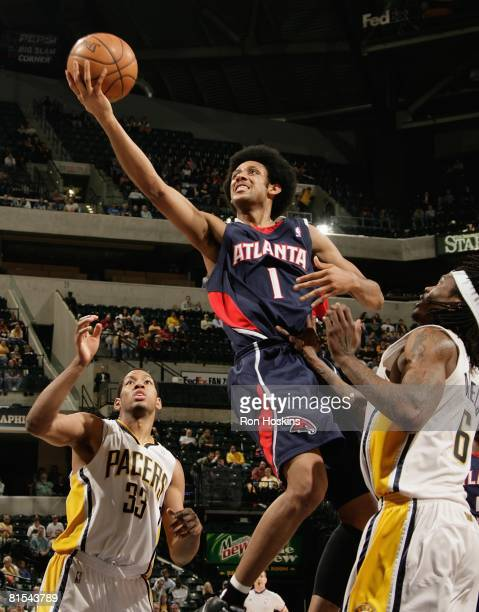 Josh Childress of the Atlanta Hawks takes the ball to the basket against Danny Granger and Marquis Daniels of the Indiana Pacers during the game at...