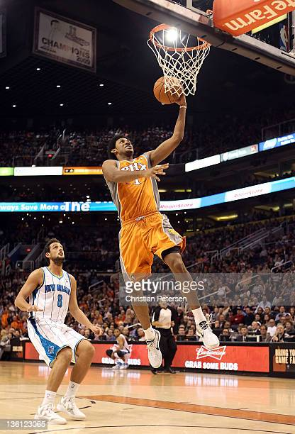 Josh Childress of the Phoenix Suns lays up a shot past Marco Belinelli of the New Orleans Hornets during the season openning NBA game at US Airways...