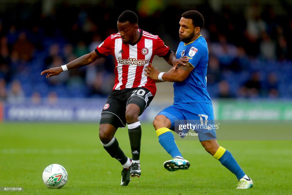 Josh Clarke of Brentford is challanged by Andy Barcham of AFC Wimbledon during the Carabao Cup First Round match between AFC Wimbledon and Brentford at The Cherry Red Records Stadium on August 8, 2017 in Kingston upon Thames, England.